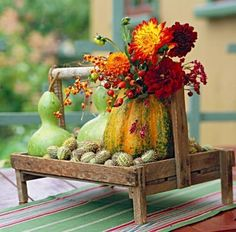 Seasons bounty - Gourds in a variety of sizes, colors, shapes and textures fill a wooden tray, accented by flowers and berries.