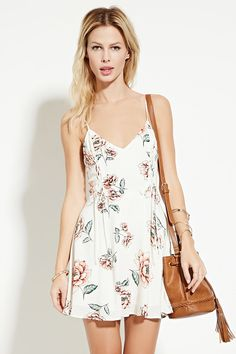 A woven mini dress with adjustable cami straps, a V-neckline, lace-up detailing on the front, an allover floral print, and a concealed back zipper.