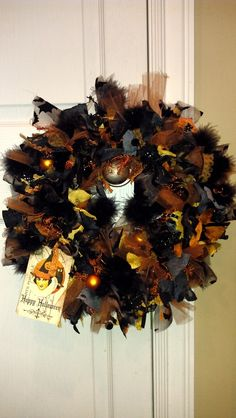 Halloween Ribbon Wreath - Variety of ribbon, tulle, cut up material, and boa feathers tied around a wire framed wreath.  Accessorized with a vintage Halloween tag, and small bulb ornaments.