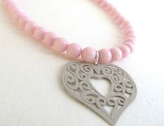 Handmade with pale pink beads and a dark cream-colored filigree heart, this bracelet adds a soft, romantic touch to any outfit.  Strung with high-quality gossamer elastic. Stretches to fit most wrist sizes.  *** Note: This bracelet is made to order. I can make it for you in any size up to 8 i...