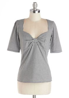 Black & white gingham top-of-the-hip length top w/ set-in half sleeves with shoulder pin tucks, sweetheart neck with pinched-center bow bust, back circle keyhole with black button tab-closure, and back princess darts. 97% cotton/3% spandex, from ModCloth, $67.99