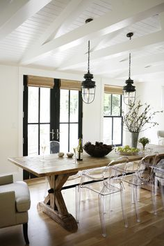 Beadboard ceiling, white beams, black accents, lantern pendants, large harvest table, modern ghost chairs with traditional armchairs. Katie Hackworth / h2 design + build