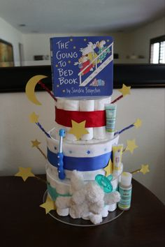 Diaper cake for a 'bring a book' themed baby shower. I started with a 4-tier acrylic cupcake stand. Filled with diaper layers then decorated with items related to the book. This particular book is a bedtime book. I decorated with a toothbrush, receiving blanket, wubbanub paci, calming lotion, calming diaper cream with lavender and calming shampoo/body wash. A few stars and a moon and voilà!