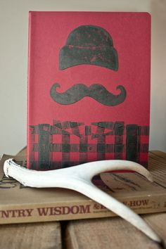 "Manly Lumberjack – Linocut Print Journal    This journal is a portable version of my ""Manly Lumberjack"" print. The print on this journal was inspired by my love of buffalo plaid and the iconic red-and-black plaid worn by a lumberjack.    This eye-catching, retro journal is a great bro accessory for any manly man.    Hand printed at 618love – Fargo, North Dakota  Moleskine Journal Specs – Red, 120 plain pages, last 16 sheets detachable, 7.5"" x 10"", acid free paper and inner pocket…"