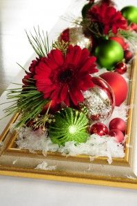 Lay an old frame on the table and fill with snow, ornaments, pine boughs, and flowers
