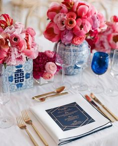 This couple made blue their central color with edged napkins, blue-and-gold menus, and blue chinoiserie vases with the double happiness character on them. To add a splash of brightness, they incorporated shades of raspberry with the centerpieces of peonies, spray lilies, and gloriosa lilies. #marthaweddings : @lizbanfield | : @makemypartyprettydod | : @adayinmay