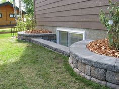 window wells landscaping - I could do  layered beds within the one big front bed.