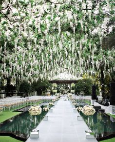 "Look at the opulent ""ceiling"" of flowers over this wedding ceremony site!"