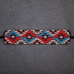 These beaded bracelets were designed and hand-loomed by crafter Charlotte Disbrowe. Charlotte is Anishinaabe from Winnipeg, Manitoba. She is from the Algonquin Ojibwe peoples. Learning from her Mom at a young age, she continues the tradition of loom beading. Inspired by her cultural heritage she designs her artwork on her bead loom using seed beads. This bracelet measures about 14 long, including the ties, and the beaded band is about 6 long and 1-1/4 wide.