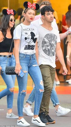 Gigi Hadid wearing Chanel Wallet on a Chain, a Gold E Sophie High Rise Skinny Jean in Cannes, Vans Leather Old School Zip Sneakers, Neff X Disney M28 T-Shirt and Minnie Mouse Ears Headband For Women