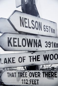 "A black & white 24""w x 48""h canvas art feature a west coast sign with directions to Banff, Mabel Lake, Nelson, Kelowna, Lake of the Woods, & That Tree Over There.  Photograph by Lindsay Nichols Photography. Sold by www.nfinteriordesign.com for $360"