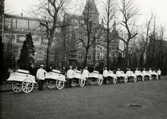 1921 NV Procto, de zuiveldistributeur.  Elf melkverkopers in hun witte jasjes staan met hun melkkarren op straat voor het Rijksmuseum. Achter hen enkele belangstellenden. Alle karren zijn van de NV Procto, de zuiveldistributeur.