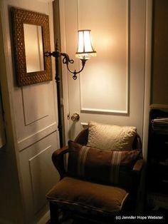 Home office, school 1950's teachers wood chair w pillows, gold frame w embossed design, antique standing brass lamp cover a closet door filled with binders not often used.  Walls a type of magnolia white with trim.