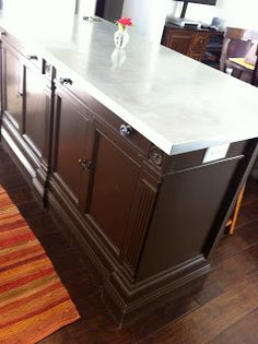 DIY kitchen island made from raising a craigslist buffet up to counter height, installing trim along the base, painting, and adding a zinc top