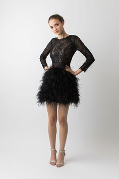Black sheer lace long sleeve feathered dress. This mini dress is the epitome of fun with its ostrich feather skirt. The bodice has princess seams to give it a close fit and the delicate black lace is sheer making it a sultry little black dress. The neckline reaches the collar bone in the front and scoops down to a v shape at the centre back finished with a lace scallop. Perfect for a night of dancing at a wedding or any event.  #cocktail #dress  #evening #feathers #floral #lace #minidress