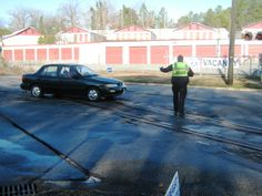 Master Officer Gorton Williams of the Roanoke Rapids Police Department tops a vehicle while directing traffic on Roanoke Avenue.