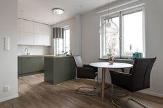 Vita köksluckor med smyckande olivgröna underskåp. Köksön är installerad med en induktionshäll och en kombiugn från Siemens | Ballingslöv