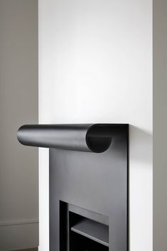 B.E Architecture curved black steel fireplace mantle at Winter Street Residence in Malvern