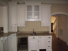 Custom White Painted Kitchen Cabinetry with Wine Glass Storage, Spice Drawers, Glass-Fronted Doors, and Mini Bar