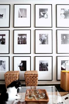 Black and white framed photographs fill a wall from the ceiling to the floor, with big chunks of negative space in the mounts to give square photos a different look (insideout.com.au)