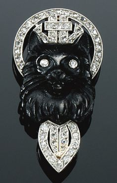 AN ART DECO ONYX CAMEO AND DIAMOND BROOCH/PIN, 1920. The onyx cameo carved to depict the profile of a cat with single-cut diamond eyes applied to an open work millegrain surround set with single- and rose-cut diamonds, maker's marks.