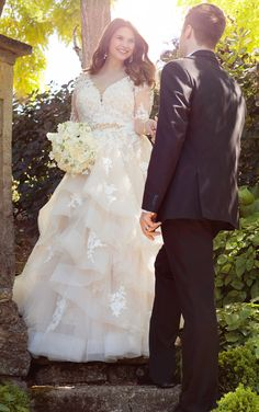 """This elegantly crafted plus size designer tulle wedding dress from Essense of Australia features alluring illusion lace sleeves and eye-catching cuts of tulle on its skirt. Choose from silver or gold Diamante embellishments. A 1.5"""" beaded grosgrain belt slims the waist. The back zips up under sparkling crystal buttons."""