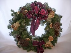 #DoorWreath with a #burgundy #ribbon and #bow, dried #fruitslices, #moss, dried #lotusheads, and #pine #cones. Christmas Flowers, Christmas Wreaths, Fruit Slices, Christmas Arrangements, Table Centers, Door Wreaths, Pine Cones, Burgundy, Bouquet
