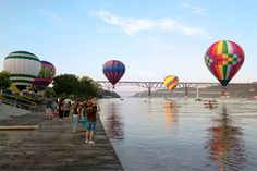 A scene from the 2013 Hudson Valley Balloon Festival. 15 multicolored hot air balloons take off from the banks of the Hudson River in Poughkeepsie, NY.