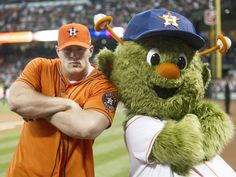 HOUSTON, TX - MARCH 31:  Defensive end J.J. Watt of the Houston Texans poses with Houston Astros mascot Orbit after throwing out the first pitch during opening night at Minute Maid Park as the Texas Rangers played the Houston Astros  on March 31, 2013 in Houston, Texas.  (Photo by Bob Levey/Getty Images) Photo: Getty Images