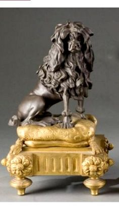 Pair of Louis XVI style ormolu and patinated bronze chenets. 19th century. One modeled as a poodle, the other a cat.