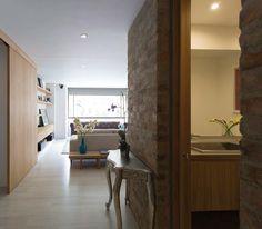 Un muro de ladrillo a la vista define la vivienda. Se extiende desde la entrada del apartamento y a lo largo de toda la zona social para culminar en la cocina.