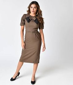 Slip into this 1940s style wiggle dress, doll! This fun piece is adorned with an adjustable belt that matches the brown and black houndstooth pattern, and has black faux buttons on the cuffed short sleeves and front collar bow. A classic ten inch slit on