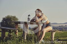 Exhausted female runner with hand on head resting on a rustic wooden bench. Pretty young woman having a headache from dehydration or overtraining. Young sporty lady having a bad training day.