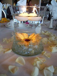 Centerpiece idea: Marbles on the bottom with a sunflower and floating candles on top.