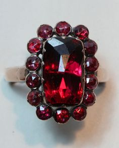 An 18 carat gold ring set with a rectangular cut rhodolite garnet surrounded by small rose cut garnets, all set on red gold foil, Perpignan, France, circa 1850.