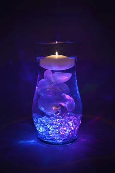 Make this awesome color changing centerpiece by burying a color changing submersible tealight under some clear gems. Fill the vase with water, add a faux (or real) orchid, and top the vase with a floating candle. Chic centerpiece and fun mood lighting all in one.
