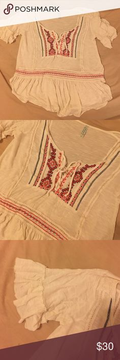 Free People Lace-Up Top From Free People. A super soft jersey top with a cute lace up detail. Bright pink and navy embroidery. Slightly sheer- looks cute over a bralette or bathing suit. Good condition - just one tiny hole as you can see in the last photo. Free People Tops Blouses