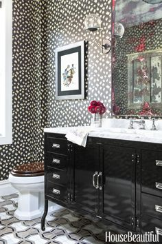In an opposites-attract powder room, a shared palette prevents the glam leopard-print wallpaper and pharmacy-style metal vanity from clashing. The distressed mirror with coral-pink streaks doesn't see daily use, so it serves mostly to inject color into the bold but limited color scheme. Click through for more powder room decorating and design ideas.