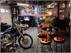 Motorcycle Man Cave inside a 2-bay garage with 2 motorcycles. Features entertainment area, bar, and pub table.