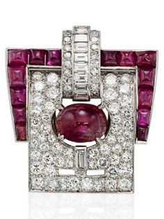 AN ART DECO CABOCHON RUBY AND DIAMOND CLIP BROOCH, CIRCA 1930. Designed as a buckle set with round, single and baguette-cut diamonds, and cabochon rubies, mounted in platinum. #ArtDeco #ClipBrooch