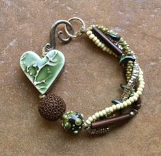 I like the raised slip design (achieved in whatever way) as component for jewelry - DIY - bracelet tutorial - heart charm Ceramic Jewelry, Clay Jewelry, Boho Jewelry, Jewelry Crafts, Beaded Jewelry, Jewelery, Jewelry Bracelets, Jewellery Box, Chain Bracelets