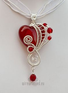 Silver plated wire and red beads, one of them heart shaped