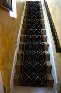 This was a standard 36″ wide roll runner from Nourison.  Made of 100% New Zealand wool, this black trellis pattern gives a boring staircase a real lift.  The stairway was 35″ wide.   Our installers trimmed a bit off the sides and it works perfectly.  The home in Newport Beach, California.  features an interior full of eclectic art.  The stairway needed a bit of a punch since it is visible from the living room.  Purchase stair runners at Hemphill's Rugs & Carpets Orange County, CA
