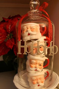Santa mugs under a cloche... with the HO HO HO, i think this is really cute!  I think i'd use a different ribbon but...