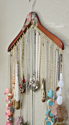 DIY Jewelry organizer. They decoupaged flowers cut from fabric to decorate the hanger, but imagine the entire hanger covered in fabric or even painted. Great idea for hanging your jewelry and keeping it neat.