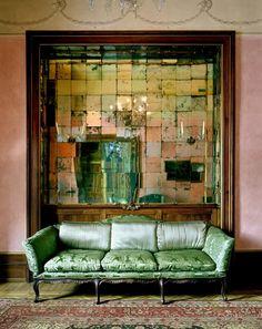 Mira este salón decorado con un mosaico de espejos combinado con este sofá de terciopelo verde, obre de Michael Eastman