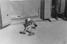 "An emaciated Warsaw Ghetto child expires slowly while begging on the streets.  This is the result of hatred and fascism under nazis/hitler.  stalin/communism led to cannibalism in Ukraine b/c the people's bread was stolen for ""the elite'"