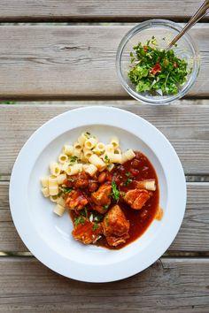 Leckerers Hühnchen, langsam in Tomatenauce geschmort, mit Bohnen und Knoblauch zu Pasta serviert.