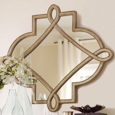 Decorative wall mirror in silver leaf with scrolling overlay detail.   Product: MirrorConstruction Material: Resin and mirrored glassColor: Gold hued silver leafFeatures: Gorgeous curving form will add elegance to any spaceDimensions: 38 H x 50 W