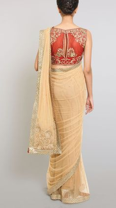 Beige Net Sari With A Stitched Blouse - A beige /red net sari with a stitched blouse and a petticoat. The Indian sari is adorned with with subtle embellishments and a heavy border. The blouse is a sleeveless red one which is adorned with gold embroidered motifs and net panels. Style this subtle evening sari with gold heels and matching accessories.